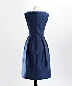 Back view of cobalt blue shantung cocktail dress with scoop neck with inset organza ruffle and pleated skirt