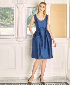 Model wearing cobalt blue shantung cocktail dress with scoop neck with inset organza ruffle and pleated skirt