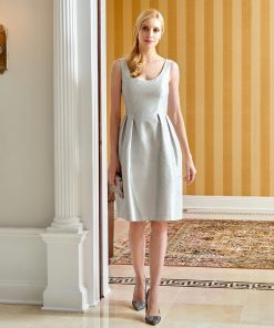 Model standing wearing silver shantung cocktail dress with scoop neck and pleated skirt