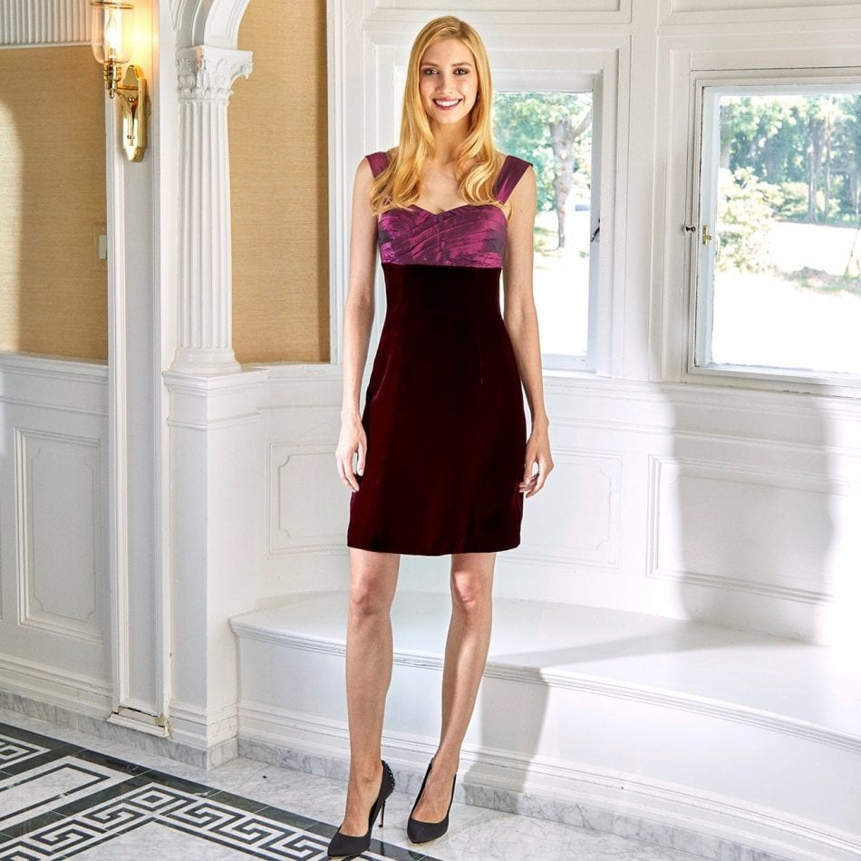 Model wearing cocktail dress with hand pleated wine taffeta bodice and wine velvet skirt standing