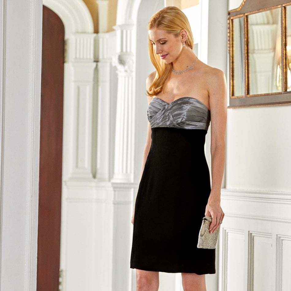 Model wearing cocktail dress with hand pleated silver taffeta bodice and black velvet skirt standing