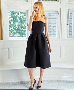 Model standing wearing black silk faille strapless cocktail dress with full skirt and organza ruffle across bodice