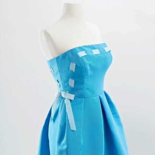 Detail shot of bodice of blue strapless silk faille cocktail dress with full skirt and light blue woven ribbon detail and bows at waist