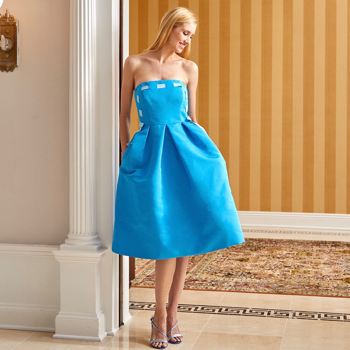 Model wearing strapless blue silk faille cocktail dress with light blue woven ribbon detail standing