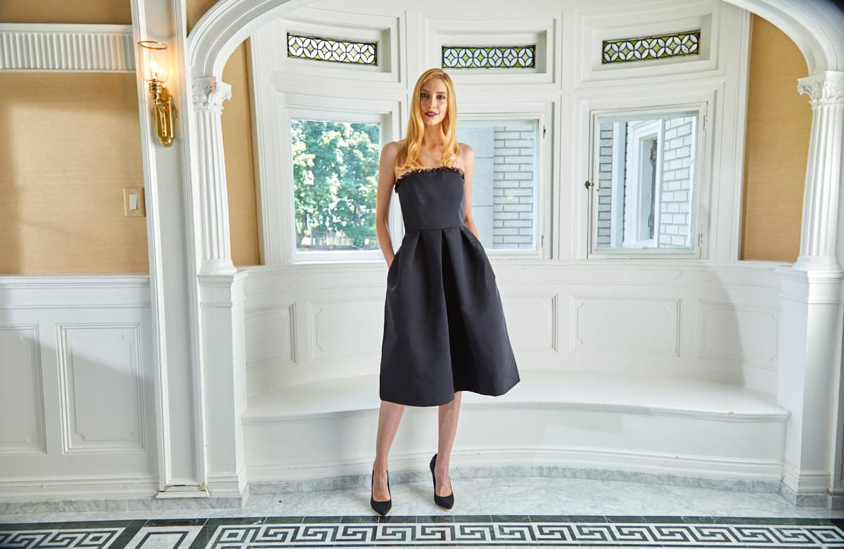Black cocktail dress on model with ruffled bodice